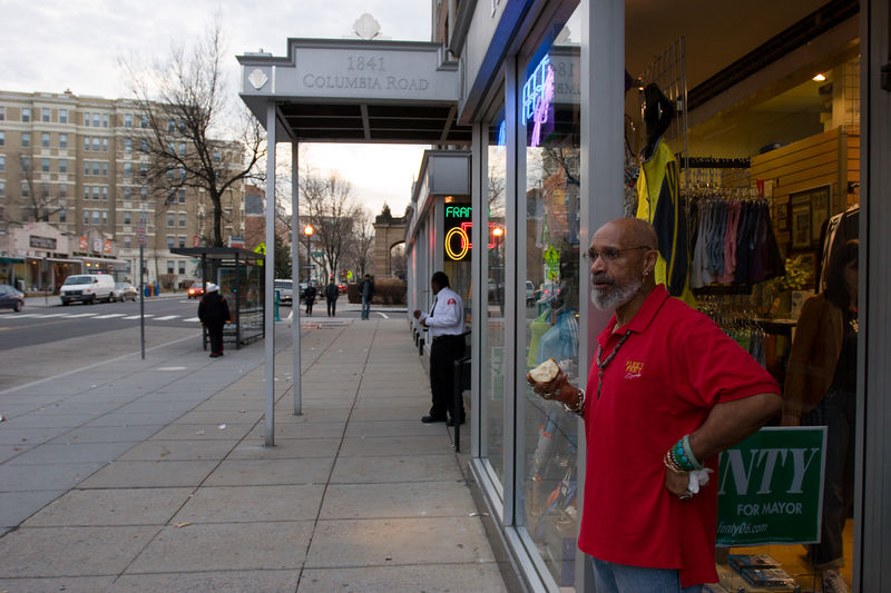Phil Fenty, snacking on a pear in front of his store, Fleet Feet, in Adams Morgan
