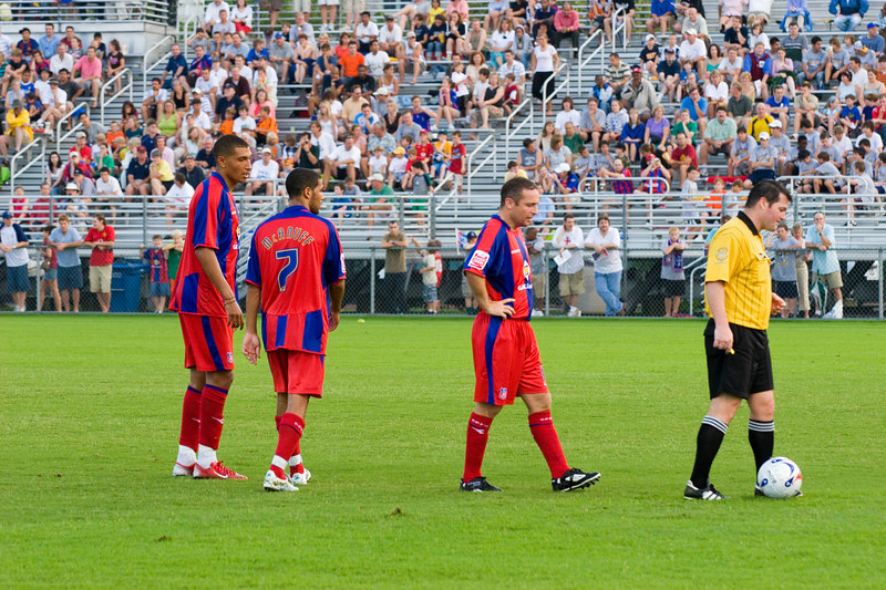 Jay Bothroyd, Jobi McAnuff and Michael Hughes line up for a free kick about 30 yards out.