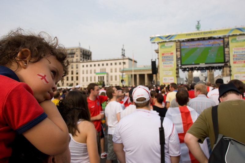 A young England fan can't bear to watch the England v. Trinidad and Tobago game on the big screen at Berlin's Fan Mile in front of the Brandenburg Gate.