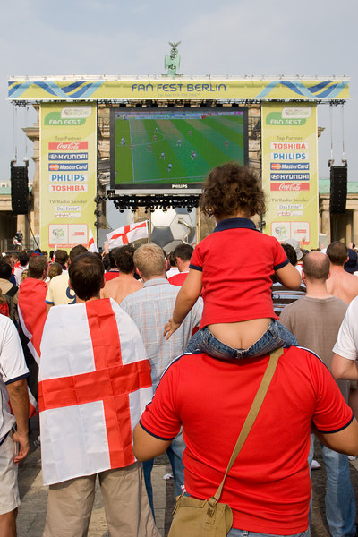 The England v. Trinidad and Tobago game is shown on the big screen at Berlin's Fan Mile, with the statue of Nike on the Brandenburg Gate just peeking out above.  England fans' confidence starts to crack during the first half as Sven's men find it hard to break down a stubborn T&T defence.