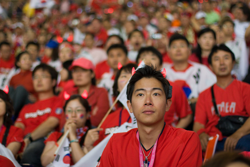 A South Korea fan at Hannover stadium with illuminated devil horns listens for the score from the France Togo match, a result which could determine his team's fate.