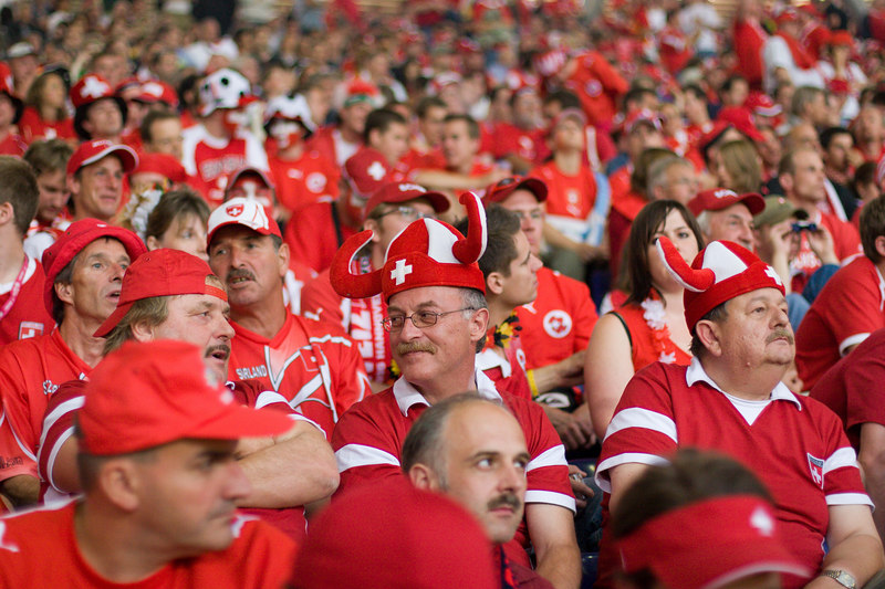 Horned Switzerland fans discuss strategy at half-time against South Korea in Hannover.