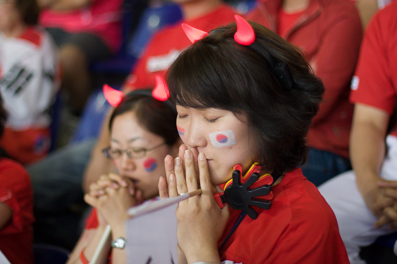 With their team losing 1-0 to Switzerland at half-time in Hannover, South Korea fans sporting illuminated Red Devil horns say a prayer.