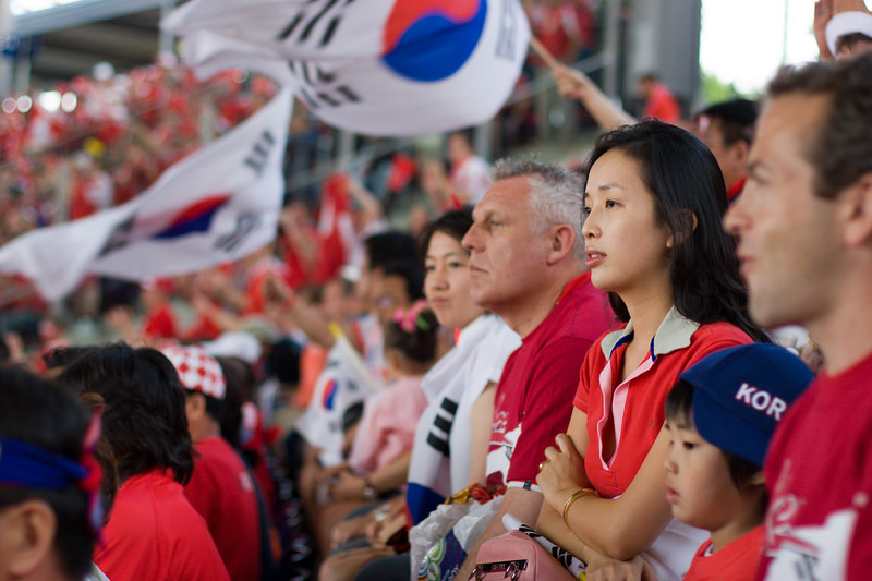 A diverse group of South Korea fans at Hannover stadium.