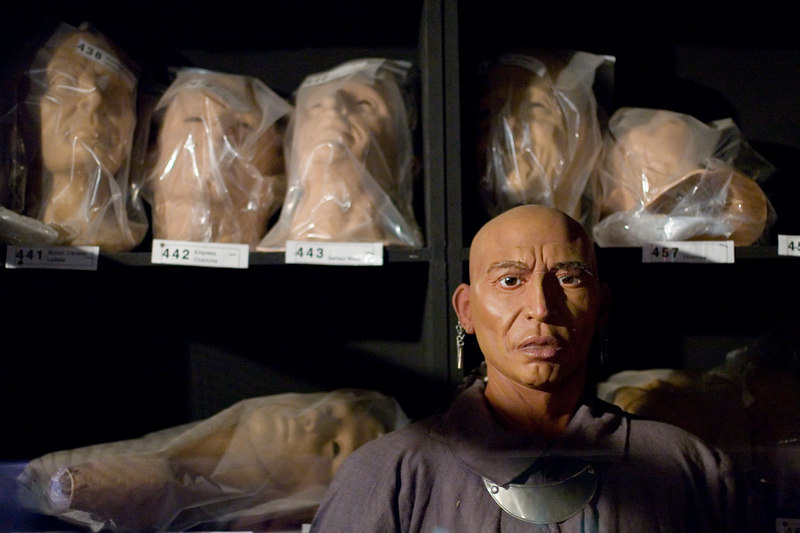 Native American wax model with shelves of latex heads behind.