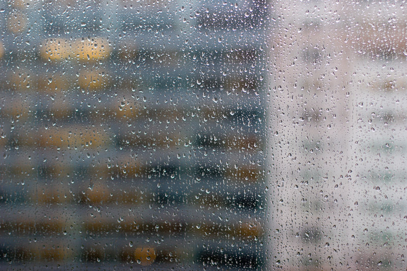 downtown office building through rain-soaked window