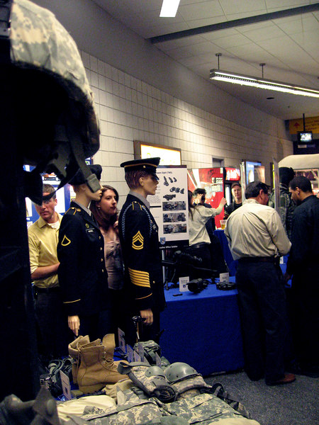 it was military appreciation night at the hockey game.  the two people behind the mannequins were working at this booth which was showcasing military uniforms and gear.  when i took my camera out of my pocket, they both suddenly moved behind the mannequins as if either seeking cover or preparing to march the mannequins out of the shot.