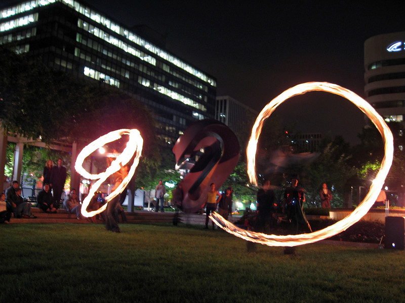 fire dancers unwittingly mimic the sculpture in the plaza