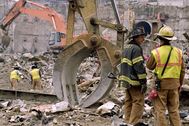New York, NY, March 15, 2002 -- Fire Department of New York personnel talk during clean-up at Ground Zero. As the six-month anniversary of the World Trade Center attack passes, the debris removal effort--a collaboration between FEMA and the city and state of New York--continues to run ahead of schedule and under budget.<br /> <br /> Photo by Larry Lerner/ FEMA News Photo