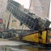 New York, NY, March 15, 2002 -- A truck dumps debris into the bucket of a 500-ton floating crane located at FEMA's Pier 25 Loading Site, a few blocks from Ground Zero. Each day, an average of 290 loads are delivered to the pier, totaling nearly 6,332 tons.   <br /> <br /> Photo by Larry Lerner/ FEMA News Photo