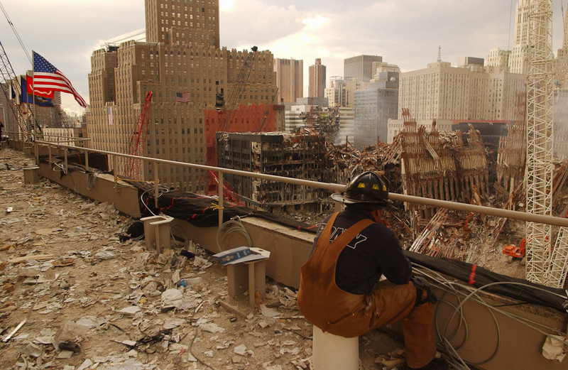 New York, NY, September 28, 2001 -- Firefighter watches debris removal at the World Trade Center from nearby roof. <br /> <br /> Photo by Andrea Booher/ FEMA News Photo
