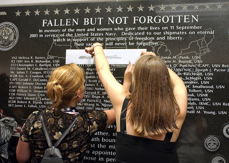 020911-N-4868G-052<br /> Pentagon, Arlington, Va., (Sep. 11, 2002) -- Family and friends of Navy personnel lost in the Sept. 11, 2001 attack on the Pentagon make pencil rubbings of the names of their lost loved ones.  The names are inscribed on a memorial dedicated on the first anniversary of the attacks.  The plaque is on permanent display near the newly reconstructed Navy Operations Center in the Pentagon.  U.S. Navy photo by Chief Photographer's Mate Philomena Gorenflo.  (RELEASED)
