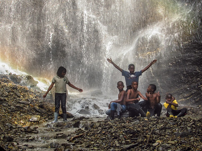 Children from La Alsacia playing in a waterfall