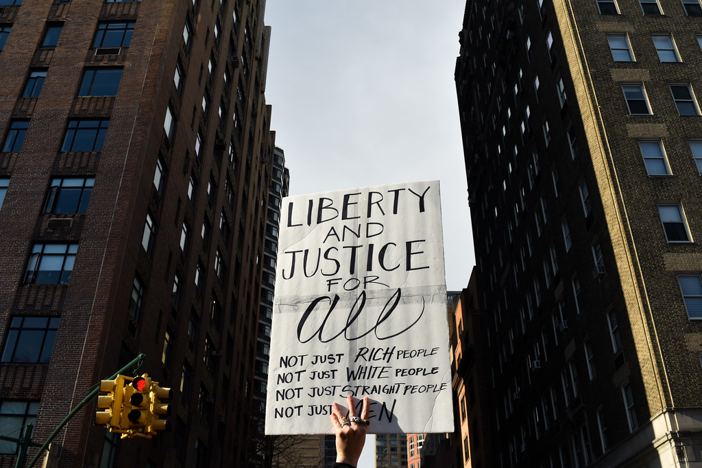 A protester holds a sign up high.