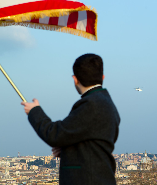 A seminarian at the Pontifical North American College waves an American flag as the helicopter carrying Pope Benedict passes by