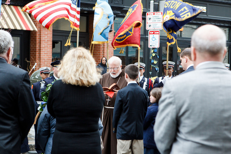 The families of the three people killed in the Boston Marathon bombing explosions — Martin Richard, Krystle Campbell and Lingzi Lu — listen as Cardinal Sean P. O'Malley proclaims a reading from Scripture before wreath-laying at the site of the first explosion April 15, the first anniversary of the attack. With the cardinal were Boston Mayor Martin J. Walsh and his partner Lorrie Higgins and Gov. Deval Patrick and his wife, Diane. (Pilot photo/ Gregory L. Tracy)