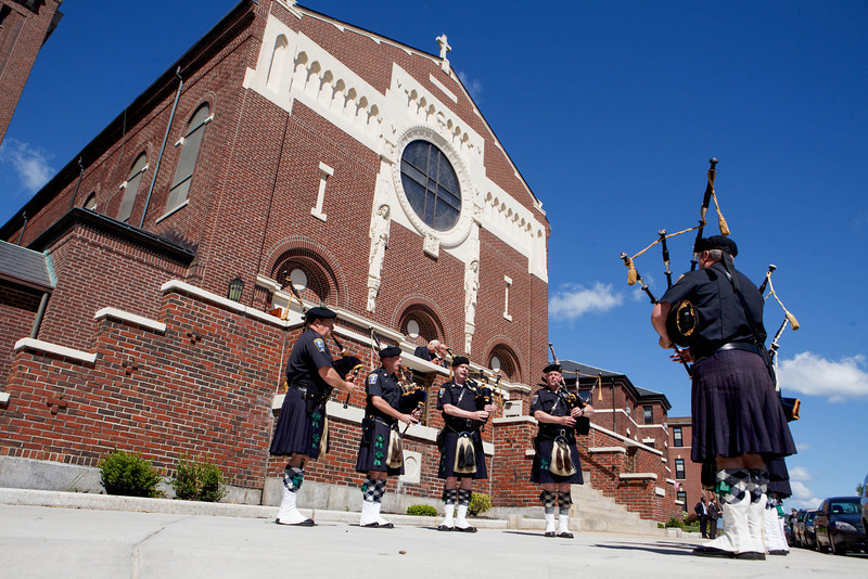 Members of the Boston Police Gaelic Column Pipe and Drum Corps Perform outside St. Ann Church in Dorchester June  9, 2013. Photo by Gregory L. Tracy, The Pilot
