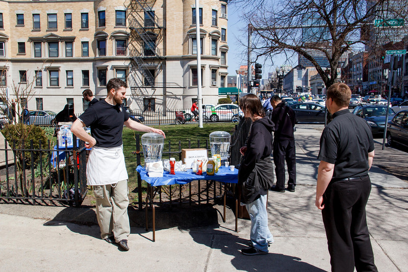 At St. Clement Eucharistic Shrine on Boylston Street in Boston, seminarians of the Oblates of the Virgin Mary and their director, Father Thomas Carzon, OMV, serve free hotdogs to people passing by the shrine on their way to the Red Sox home opener at Fenway Park April 8. Seminarian Joshua Kingdon welcomes a pedestrian to have a hotdog. As an outreach effort during the Year of Faith, the oblates served over 400 hotdogs, offered tours of the shrine, and spoke about the Catholic faith with passersby.<br /> Pilot photos by Christopher S. Pineo