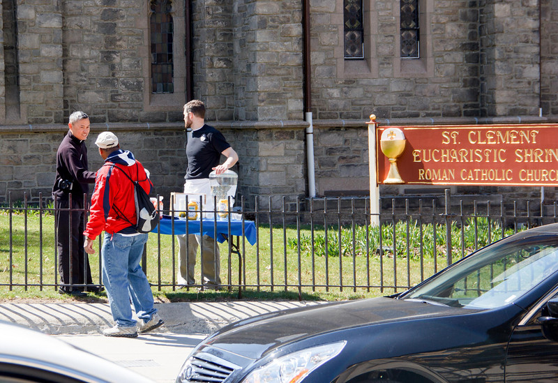 At St. Clement Eucharistic Shrine on Boylston Street in Boston, seminarians of the Oblates of the Virgin Mary and their director, Father Thomas Carzon, OMV, serve free hotdogs to people passing by the shrine on their way to the Red Sox home opener at Fenway Park April 8.  As an outreach effort during the Year of Faith, the oblates served over 400 hotdogs, offered tours of the shrine, and spoke about the Catholic faith with passersby.<br /> Pilot photos by Christopher S. Pineo
