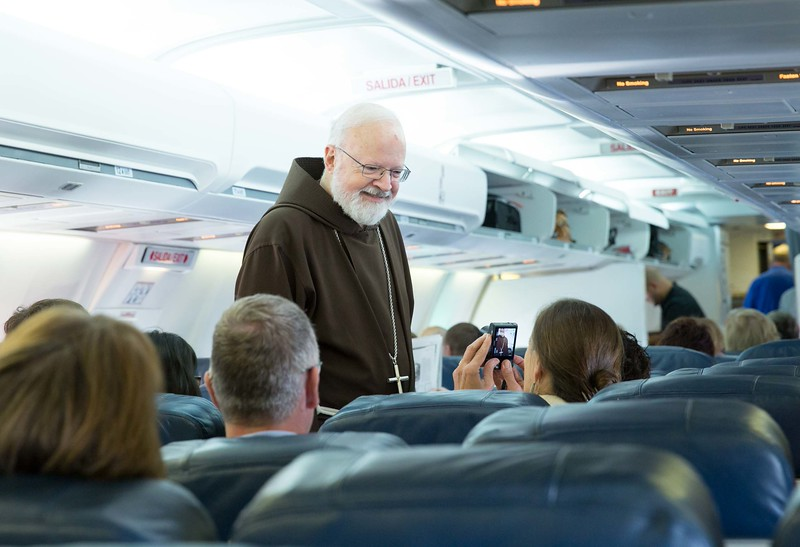 Cardinal O'Malley greets passengers aboard the plane heading to Havana to attend the Mass celebrated by Pope Francis Sept. 20.<br /> Pilot photo/ Gregory L. Tracy