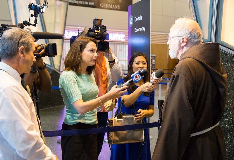 Cardinal O'Malley answers questions for the media before passing through the security checkpoint at Logan Airport.<br /> Pilot photo/ Gregory L. Tracy