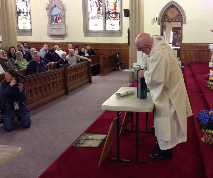 Deacon Norman LaPointe opens the time capsule.<br /> Courtesy photo