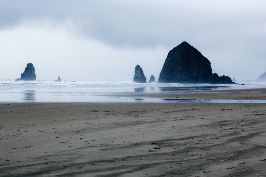 MARCH  2011<br /> <br /> This photograph was taken on Cannon Beach on the Oregon coast. <br /> <br /> The rain was relentless and I while I was soaked to the bone, I simply didn't care.  This beach is gorgeous even in the rain.  I love how the light is brighter on the horizon - a sign that the sun and spring are sure to return soon!