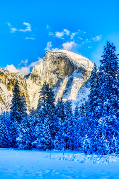 A snowy Half Dome in the afternoon sunlight