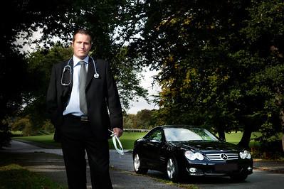 Mand i jakkesæt og med stetoskop og læge mundbind ved dyr bil. Illustration af læge med job både i offentlig og privat sygehus, Århus, Modelfoto