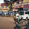 Bodas (motorcycle taxis) in front of the Jinja Central Market.  Law requires all drivers to be licensed, carry only one passenger, and provide helmets, but the financial situation of many drivers means that often all three of those rules are ignored at once.