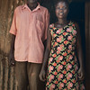 Sulama, one of X-SUBA's sponsored students, with her father at their home.  Her mother makes hand brooms and her father burns trash, which hardly pays enough to send her to school.  Thanks to the sponsorship program, she just finished primary school and will soon be attending secondary school.
