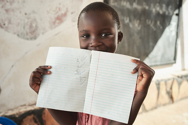 A young student showing off her progress with the alphabet at X-SUBA's Learning Center.  English is taught once a week to students whose parents can't afford to send them to school.  Math and Critical Thinking are taught on two other days of the week.  The children are only allowed to stay at the Learning Center for one year so as to not overwhelm the volunteers.  They use this time to teach the parents about budgeting and look for sponsors to send the kids to primary school.