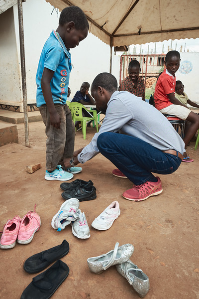 Coach Kenneth helps Emma try on some new shoes that he brought back from a recent trip to London.  Emma didn't have any shoes at the beginning of the day.