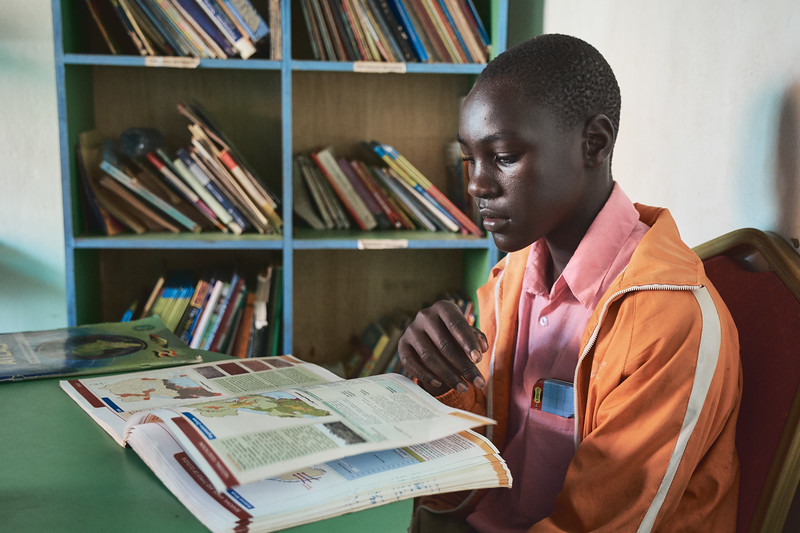 X-SUBA's Learning Center has a small library where children can look at textbooks and other educational materials - all donated.  Here, a primary school student studies a geography textbook.  He is attending school thanks to X-SUBA's sponsorship program.  His two younger brothers are currently Learning Center students and hoping to get sponsored as well.