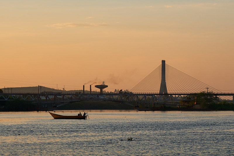 Fishing boats setting out at dusk on the Nile River near Jinja, with the new Source of the Nile Bridge in the background.
