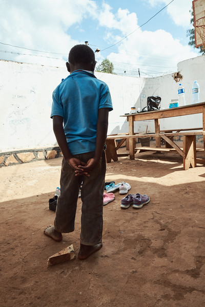 Coach Kenneth brought back some donated children's shoes from a recent trip to London.  It's difficult to prioritize which children should get new shoes, but he starts with the ones who have none at all.  Here Emma is the first to pick and examines his choices.