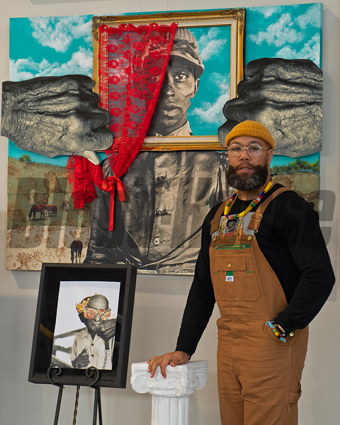 Standing in front of his large piece called Behind The Roses. The smaller piece, below left, is called What They Didn't See.<br /> Dafri, an American artist, at Greyline where his artwork is displayed and sold in Lexington, Ky. on March 11, 2021.