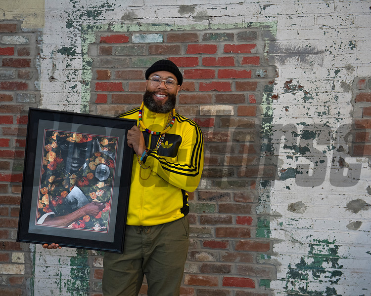 holding print of HIdden Flowers.<br /> Dafris the artist in his booth at Greyline in Lexington, Ky., on March 4, 2021.