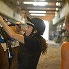 Caption: student Chelsea Pizzuto checks tack before getting a leg up from instructor Amy Heitzman<br /> BCTC equine school and NARA in Lexington, Ky., and Thoroughbred Training Center, on July 6, 2020 BCTC in Lexington, KY.