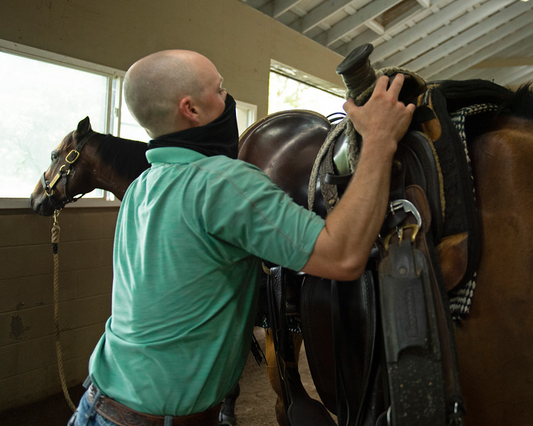 Caption:  After training the last set, Heath unsaddles his pony Fred as his other pony Stumbles looks out the window. <br /> A native of Oklahoma, Heath started working at WinStar Farm on October 10, 2014, and became the farm trainer in October of 2018. Presently he has about 100 horses in training at the WinStar Farm training center, where they have a 7 1/2-furlong main track and 3/4 of a mile undulating turf gallop.<br /> Daily Life series on Destin Heath, farm trainer at WinStar Farm on Aug. 11, 2020 WinStar Farm in Versailles, KY.