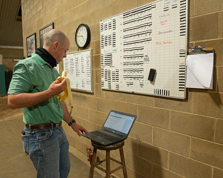 Caption: While eating a banana, Destin reviews the computer version of his daily sets before printing out a copy for each barn to have for quick reference.<br /> A native of Oklahoma, Heath started working at WinStar Farm on October 10, 2014, and became the farm trainer in October of 2018. Presently he has about 100 horses in training at the WinStar Farm training center, where they have a 7 1/2-furlong main track and 3/4 of a mile undulating turf gallop.<br /> Daily Life series on Destin Heath, farm trainer at WinStar Farm on Aug. 11, 2020 WinStar Farm in Versailles, KY.