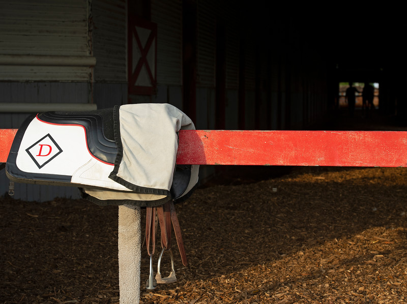 Caption: Drury saddle at barn as horse is walked in background. <br /> trainer Tommy Drury at Skylight Training Center ton Aug. 12, 2020 Skylight Training Center in Prospect, KY.