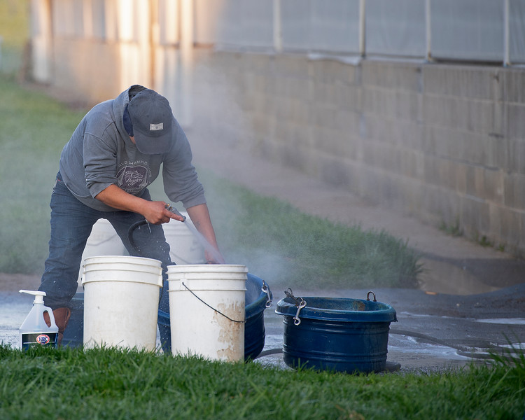 Caption: cleaning feed tubs in Breeders' Cup sweatshirt<br /> Behind the Scenes at Keeneland during Covid19 virus and the people, horses, and essentials needed to take care of race horses on April 2, 2020 Keeneland in Lexington, KY.
