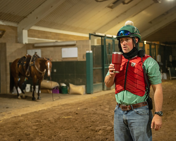 Caption: Coffee break after first set at 5:54 am as pony Fred waits in background<br /> A native of Oklahoma, Heath started working at WinStar Farm on October 10, 2014, and became the farm trainer in October of 2018. Presently he has about 100 horses in training at the WinStar Farm training center, where they have a 7 1/2-furlong main track and 3/4 of a mile undulating turf gallop.<br /> Daily Life series on Destin Heath, farm trainer at WinStar Farm on Aug. 11, 2020 WinStar Farm in Versailles, KY.