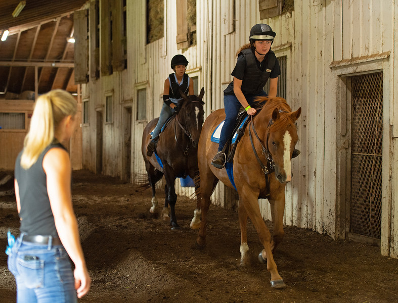 Caption: instructor Amy Heitzman, left, watches as Chelsea Pizzuto, front on chestnut, and Camille Hargrove on dark bay. <br /> BCTC equine school and NARA in Lexington, Ky., and Thoroughbred Training Center, on July 6, 2020 BCTC in Lexington, KY.