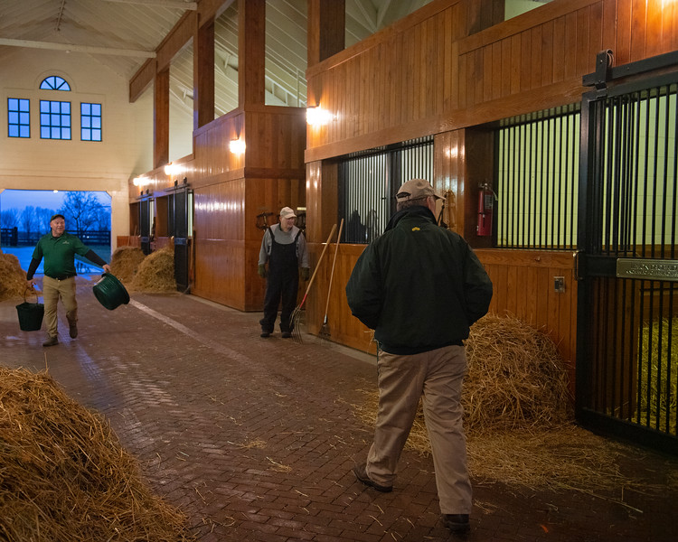 Caption: 7:20 am:  Billy, right, makes his rounds through the stallion barns to check on the stallions and check in with his team for any specific changes or notations. Daily Life on Billy Sellers, Lane's End Farm stallion manager who started working for the farm in 1982 and who has been their only stallion manager since 1985 when the farm acquired their first stallions, photographed on<br /> March 3, 2020 Lane's End Farm in Versailles, KY.