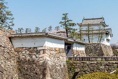 The omote-ninomon gate. An older style Koraimon wooden gate way through ishigaki, stone wall with the Tatsumi yagura in the background.