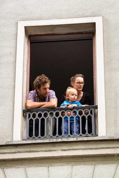 Residents of an upper story apartment go to the window to watch the procession.