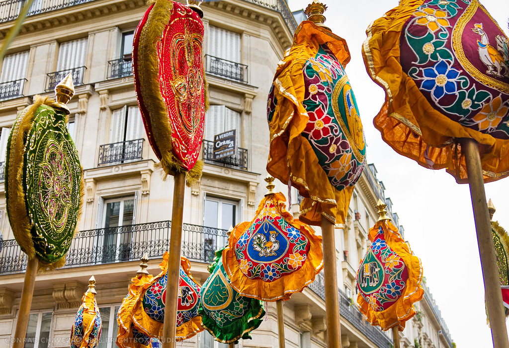 The procession is led by devotees carrying ornate and colorful pillow-like decorations on poles.