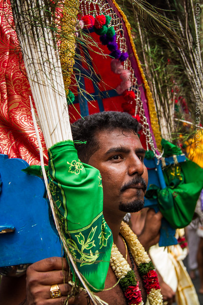 A man carries the front half of a decorated procession object.